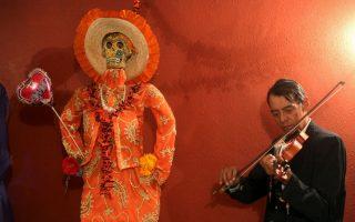 Μουσική για την Catrina. Αν και οι περισσότεροι οπαδοί της Γιορτής των Νεκρών, δηλώνουν φανατικοί καθολικοί, στην πραγματικότητα γιορτάζουν μια παγανιστική τελετή με ρίζες από τους Αζτέκους και τους Μάγια και τους δικούς τους Θεούς του Θανάτου. Στην φωτογραφία το άγαλμα της La Santa Muerte  στολίζει μια γιορτή στην Ciudada Juarez, όπου ζευγάρια ντυμένα και βαμμένα σαν σκελετοί, γιόρτασαν μια από τις πιο χαρακτηριστικές και πολύχρωμες γιορτές του Μεξικού. REUTERS/Jose Luis Gonzalez