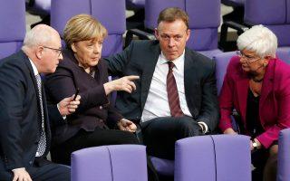 Η Μέρκελ μιλάει με τους κοινοβουλευτικούς εκπροσώπους Φόλκερ Κάουντερ και Τόμας Οπερμαν.