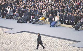 Στον βαρύ από ιστορικές μνήμες χώρο των Invalides, ο Φρανσουά Ολάντ κατευθύνεται προς το βήμα του μνημοσύνου για τους 130 ανθρώπους που έπεσαν θύματα των τρομοκρατικών επιθέσεων την 13ης Νοεμβρίου.