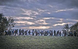 Ομάδα προσφύγων οδηγείται από άνδρες της σλοβενικής αστυνομίας σε κέντρο καταγραφής της Ντομπόβα, κοντά στα σύνορα με την Κροατία. Το σημερινό προσφυγικό κύμα χαρακτηρίζεται το μεγαλύτερο στην Ιστορία, με περισσότερους από 60 εκατ. ανθρώπους να έχουν εγκαταλείψει τις εστίες τους.