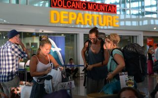 Passengers wait to obtain information on delayed and cancelled flights at the international departure area of Bali's Ngurah Rai Airport in Denpasar on November 5, 2015. Bali's international airport will remain closed until  on November 6 due to ash erupting from a nearby volcano, Indonesian officials said, grounding hundreds of flights for a second consecutive day.  AFP PHOTO / SONNY TUMBELAKA