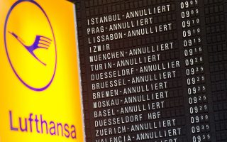 A board displaying cancelled Lufthansa flights can be seen behind the logo of German airline Lufthansa on November 11, 2015 at the airport in Frankfurt am Main, western Germany. A German court late Tuesday, November 10, 2015 gave the green light for Lufthansa's cabin staff to continue their strike, in what is set to be the worst industrial action in the history of the country's biggest airline.     AFP PHOTO / DPA / BORIS ROESSLER   +++   GERMANY OUT   +++