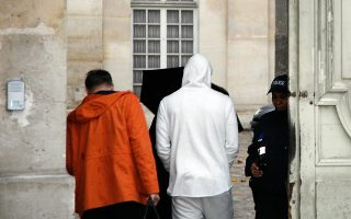 French footballer Karim Benzema (C), wearing a white hooded jersey, arrives at the police station in Versailles, southwest of Paris, on November 4, 2015. French footballer Karim Benzema was arrested on November 4 in connection with blackmail over a sextape featuring fellow player Mathieu Valbuena, a source close to the probe told AFP. AFP PHOTO / MATTHIEU ALEXANDRE