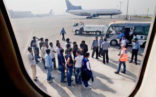 Μετανάστες οι οποίοι απελάθηκαν από την Ελλάδα το 2012, κατά την άφιξή τους στο αεροδρόμιο της Λαχώρης, στο Πακιστάν, παραδίδονται στους τοπικούς αστυνομικούς.
