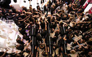 Υπάλληλοι σε κατάστημα της εταιρείας H&M στη Νέα Υόρκη, ετοιμάζονται με έναν δικό τους ιδιαίτερο τρόπο –ασκήσεις ψυχραιμίας, ίσως;– να υποδεχθούν το κοινό.