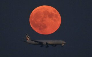 epa04954059 An Air France jetliner is approaching to a runway for landing under a so-called 'Supermoon' at Tokyo International Airport at Haneda in Tokyo, Japan, 28 September 2015. The 'Supermoon' can be seen when the moon makes closest approach to the Earth, this time coinciding with a total lunar eclipse.  EPA/KIMIMASA MAYAMA