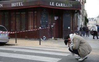 Μια γυναίκα  θρηνεί μπροστά στο καφέ «Λε Καριγιόν», όπου 14 άνθρωποι βρήκαν τον θάνατο τη νύχτα της Παρασκευής από τα πυρά των Καλάσνικοφ των τρομοκρατών.