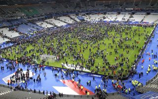 Spectators invade the pitch of the Stade de France stadium after the international friendly soccer France against Germany, Friday, Nov. 13, 2015 in Saint Denis, outside Paris. Multiple fatal attacks throughout the city have prompted President Francois Hollande to announce he was closing the country's borders and declaring a state of emergency. (AP Photo/Michel Euler)