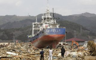 FILE - In this April 2, 2011 file photo, survivors look at a ship among the rubble at a March 11 earthquake and tsunami-destroyed area in Kesennuma, Miyagi prefecture, Japan. The stranded fishing boat that became a symbol of the devastation of Japan's 2011 tsunami has long divided a northeastern coastal city - between those who wanted to keep it as a monument of survival and those who wanted a painful reminder gone. Last week, the city announced it will be torn down after a heated debate and citywide vote. (AP Photo/Lee Jin-man, File)