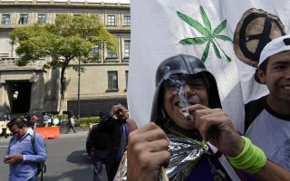 Αντρας καπνίζει μαριχουάνα σε διαδήλωση μπροστά από το κτίριο του ανώτατου δικαστηρίου του Μεξικού.
