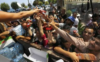 Syrian refugees and other migrants struggle to get dry food during aid distribution by workers of the Kos municipality on the Greek island of Kos August 14, 2015. United Nations refugee agency (UNHCR) called on Greece to take control of the