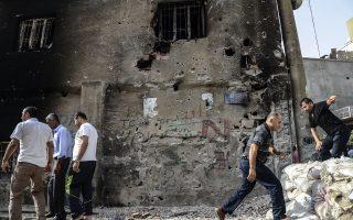 Πολίτες επιθεωρούν τις καταστροφές στην κουρδική πόλη Τσίζρε, σε μια ανάπαυλα των εχθροπραξιών μεταξύ στρατού και ανταρτών του ΡΚΚ. Τουλάχιστον 18 άνθρωποι σκοτώθηκαν χθες στη νοτιοανατολική Τουρκία.