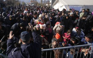 Serbian police officer attempt to organise migrants queuing to get registered at a refugee center in the southern Serbian town of Presevo, Monday, Nov. 16, 2015. Refugees fleeing war by the tens of thousands fear the Paris attacks could prompt Europe to close its doors, especially after police said a Syrian passport found next to one attacker's body suggested its owner passed through Greece into the European Union and on through Macedonia and Serbia last month. (AP Photo/Darko Vojinovic)