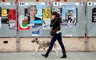 Γυναίκα κάνει βόλτα τον σκύλο της μπροστά σε προεκλογικές αφίσες υποψηφίων της «Ιλ ντε Φρανς» στο Παρίσι.