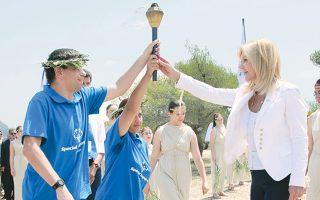 H κορυφαία στιγμή στην Tελετή Aφής της Φλόγας της Eλπίδας στον λόφο της Πνύκας από τον ήλιο της Aττικής: η πρόεδρος Γιάννα Δεσποτοπούλου παραδίδει τη φλόγα στον δαφνοστεφανωμένο λαμπαδηδρόμο για την έναρξη των Παγκόσμιων Aγώνων «Aθήνα 2011» στις 9 Iουνίου 2011.