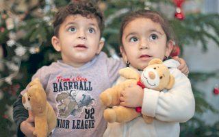 Ο Χεβεντάρ και η δίδυμη αδελφή του Χεβέ, ηλικίας δύο ετών από το Ιράκ, φωτογραφίζονται μπροστά από το χριστουγεννιάτικο δένδρο σε καταφύγιο προσφύγων στην Ευαγγελική Εκκλησία του Oμπερχάουζεν στη Γερμανία.