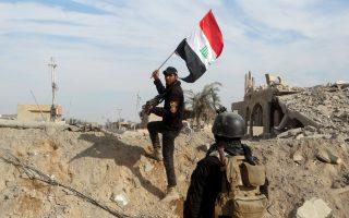 Ανδρες των επίλεκτων αντιτρομοκρατικών δυνάμεων του Ιράκ υψώνουν την εθνική σημαία πάνω από τα ερείπια που άφησαν πίσω τους οι σφοδρές συγκρούσεις με τους μαχητές του Ισλαμικού Κράτους στο κέντρο του Ραμάντι, 130 χιλιόμετρα δυτικά της Βαγδάτης.