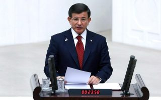 Turkish Prime Minister Ahmet Davutoglu (front) reads the government's program during a session of the Turkish Parliament in Ankara, on November 25, 2015. Davutoglu on November 25 said his government did not want to fuel tensions with