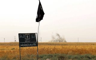 (FILES) This file photo taken on September 11, 2015 shows smoke rising in the distance behind an Islamic State group (IS) flag and banner after Iraqi Kurdish Peshmerga fighters reportedly captured several villages from IS group jihadists in the district of Daquq, south of the northern Iraqi multi-ethnic city of Kirkuk. From the blood spilled in the streets of Paris to the San Bernardino shootings, the world in 2015 showed its vulnerability to the brand of terror perpetrated by Islamic State jihadists.Over the past 12 months, the group that took root in Iraq and in the chaos of the Syrian war has turned its focus from territorial gains to hitting at