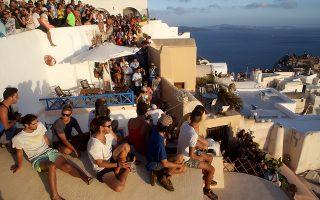 Τουρίστες έχουν πάρει θέση στην Οία προκειμένου να παρακολουθήσουν το ηλιοβασίλεμα.
