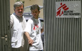 The Medecins sans Frontieres aid group is to pull out of Afghanistan after more than 20 years due to security concerns and lack of progress in an investigation into the killing of five staff, a spokeswoman said July 28, 2004. Afghan staff of Medecins sans Frontieres (MSF) in Afghanistan stand at the MSF compound gates in this file photo taken in Kabul June 3, 2004.    REUTERS/Ahmad Masood/File Photo