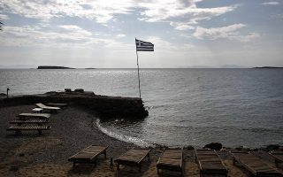 A Greek flag flutters at a beach of Voula, a suburb southeast of Athens May 10, 2014. Greece's plan to allow more construction and business activity along its vast Mediterranean coastline to boost its economy has sparked uproar in a country whose pristine beaches attract millions of tourists each year. Greece's long coastline remains less developed than other Southern Europe peers like Spain and a draft bill proposes swifter permits for beachside hotels and eases restrictions on setting up umbrellas, drink stands and sun beds. Picture taken on May 10, 2014.  REUTERS/Yorgos Karahalis (GREECE - Tags: POLITICS BUSINESS TRAVEL)