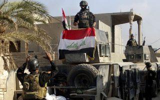 Δυνάμεις Ασφαλείας του Ιράκ υψώνουν τη σημαία στο Ραμάντι. (AP Photo/Osama Sami)