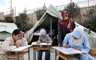 A teacher watches as Lebanese students take their entrance exam next to tents installed in the playground of a school that was damaged following Israeli forces' bombardment during the 34-day long Hezbollah-Israel conflict, in the southern village of Aynata, Lebanon, Monday, Oct. 9, 2006. Students in Lebanon started their first day at school as private schools opened Monday, except for some schools in the southern suburb of Beirut and in some towns and villages of southern Lebanon, which were still under reconstruction after they were damaged or destroyed during Israel's summertime bombardment of Lebanon. (AP Photo/Mohammed Zaatari)