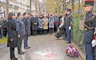 Ο Γάλλος πρόεδρος Φρανσουά Ολάντ, η δήμαρχος του Παρισιού Αν Ινταλγκό και ο πρωθυπουργός Μανουέλ Βαλς κοιτούν μια αναμνηστική πλάκα που αναρτήθηκε στο σημείο όπου δολοφονήθηκε Γάλλος αστυνομικός κατά τις περυσινές επιθέσεις εναντίον του σατιρικού περιοδικού Charlie Hebdo.