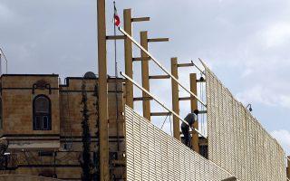 Κατασκευή σιδερένιου φράχτη γύρω από την ιρανική πρεσβεία στη Σαναά. Ιρανός φρουρός στην πρεσβεία είναι μεταξύ των χιλιάδων θυμάτων της σαουδαραβικής πολεμικής εκστρατείας.