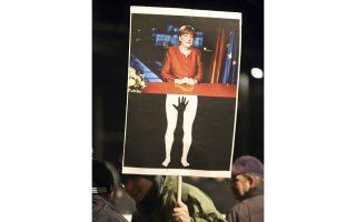 Μέλος της LEGIDA κρατάει πανό που δείχνει τη Μέρκελ ως θύμα σεξουαλικής κακοποίησης από μαύρα χέρια.