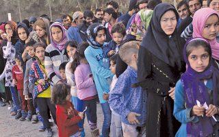 Πρόσφυγες και μετανάστες στο Κέντρο Καταγραφής, στη Μόρια της Λέσβου.