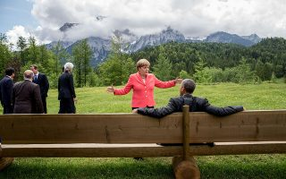 Germany's Chancellor Angela Merkel (C) gestures while chatting with US President  Barack Obama sitting on a bench outside the Elmau Castle after a so-called outreach meeting at a G7 summit near Garmisch-Partenkirchen, southern Germany, on June 8, 2015. AFP PHOTO / POOL / MICHAEL KAPPELER