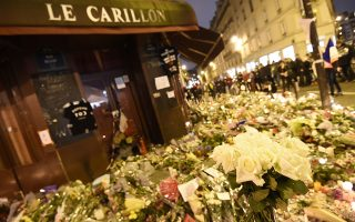 People walk past flowers and candles placed outside Le Carillon cafe, on November 16, 2015 at the corner of Rue Bichat and Alibert in the 10th arrondissement, in tribute to the victims of the Paris attacks claimed by Islamic State which killed at least 129 people and left more than 350 injured on November 13.  AFP PHOTO / MIGUEL MEDINA