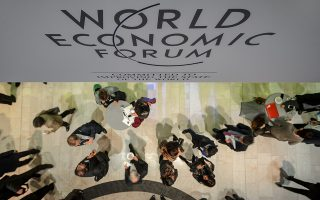 Participant are seen at the Congress Center during the World Economic Forum (WEF) annual meeting on January 21, 2014 in Davos. Top economists in Davos clashed over the impending decision by the ECB to buy up sovereign debt, an unprecedented measure to fight deflation that powerful Germany believes would merely allow overspending eurozone states to put off reforms.  AFP PHOTO / FABRICE COFFRINI