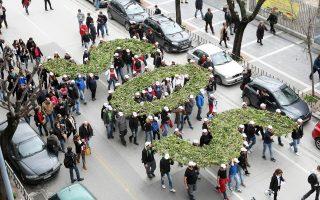 Διαδηλωτές κρατούν γράμματα–κατασκευές που σχηματίζουν τη λέξη SOS, κατά τη διάρκεια πορείας στη Θεσσαλονίκη, διαμαρτυρόμενοι για τη λειτουργία των μεταλλείων χρυσού στις Σκουριές στη Χαλκιδική.