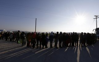 People form a line as they wait to receive food distributed by non-governmental organizations at a refugee camp in the northern Greek village of Idomeni Thursday, Jan. 21, 2016. About 1,000 refugees from Syria, Afghanistan and Iraq are stranded at Greece's northern border with Macedonia, after Macedonian authorities stopped letting them through citing problems with transit flows further north on the Balkan route which have caused a chain reaction. (AP Photo/Thanassis Stavrakis)