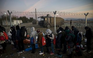 epa05058525 Migrants wait in line in front of a fence, set up by Macedonian authorities, and a Macedonian armoured vehicle on the Greek side of the border between Greece and Macedonia, near the Greek village of Idomeni, 07 December 2015. Macedonian authorities allow only migrants from war-torn countries and heading for rich EU states to cross the country while citizens of other states regarded as economic migrants are blocked by a fence built by Macedonia along this section of the border.  EPA/ZOLITAN BALOGH HUNGARY OUT