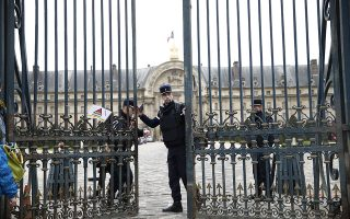epa05071095 Police officers stand guard in the courtyard of the Invalides in Paris, France, 16 December 2015, after a man tried to force the entrance with his car. A police officer reportedly opened fire on the car and the driver has been arrested.  EPA/YOAN VALAT