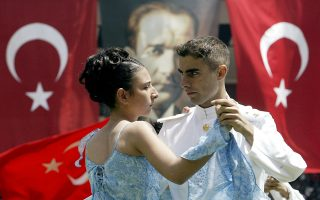 (FILES) A couple dances in front of giant Turkish flags and a giant poster of Ataturk, founder of the Turkish Republic, during the Youth and Sport Festival celebrations at Inonu Stadium, downtown Istanbul, 19 May 2004. After more than 40 years at Europe's doorstep, Turkey eagerly awaited 05 October 2004 the European Commission's green light to begin membership talks with the European Union -- but with some strings attached. The commission will issue a criticial report Wednesday on Turkey's progress in embracing European norms and it is widely expected to say Ankara is ready to begin entry talks, but also warn that talks could be suspended if EU officials believe the reforms undertaken by Turkey are compromised. AFP PHOTO FILES AFP PHOTO/Mustafa Ozer == more pictures available in Image Forum