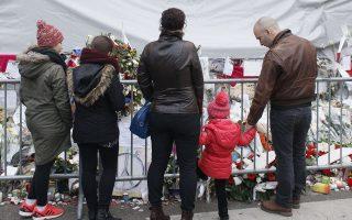 Πολίτες προσέρχονται στο θέατρο Bataclan του Παρισιού για να αφήσουν λίγα άνθη σ' ένα από τα σημεία που έγιναν στόχος τρομοκρατών τη 13η Νοεμβρίου 2015.
