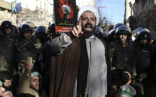 Surrounded by policemen, a Muslim cleric addresses a crowd during a demonstration to protest the execution of Saudi Shiite Sheikh Nimr al-Nimr, shown in the poster in background, in front of the Saudi embassy in Tehran, Iran, Sunday, Jan. 3, 2016. Saudi Arabia announced the execution of al-Nimr on Saturday along with 46 others. Al-Nimr was a central figure in protests by Saudi Arabia's Shiite minority until his arrest in 2012, and his execution drew condemnation from Shiites across the region. (AP Photo/Vahid Salemi)