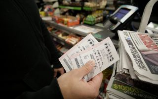 CHICAGO, IL - JANUARY 9 : A customer shows off his Powerball tickets at a 7-Eleven store January 9, 2016 in Chicago, Illinois. The Powerball Jackpot Surged to a record $900 Million in 44 States, Washington D.C., Puerto Rico, and the US Virgin Islands before tonight's drawing.   Joshua Lott/Getty Images/AFP== FOR NEWSPAPERS, INTERNET, TELCOS & TELEVISION USE ONLY ==