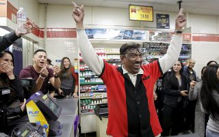 7-Eleven store clerk M. Faroqui celebrates after selling a winning Powerball ticket was sold is shown in Chino Hills, California January 13, 2016. A winning ticket was sold there for the massive $1.59 billion Powerball lottery on Wednesday, officials said after drawing the winning numbers for the world's largest potential jackpot for a single player. REUTERS/Alex Gallardo      TPX IMAGES OF THE DAY