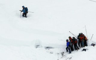 epa05101396 Members of a rescue team search in the snow for missing people after an avalanche swept away a group of people that included a party of schoolchildren, in Les Deux Alpes, France, 14 January 2016. At least three people are dead, including two children and a skier who was unattached to the school group, said officials from the local prefect. Three people were also seriously injured, reported police.  EPA/SEBASTIEN NOGIER