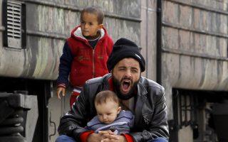 Πρόσφυγας με τα παιδιά του σε πλατφόρμα τρένου με προορισμό τη Σερβία, στο κέντρο διέλευσης προσφύγων στη Γευγελή της ΠΓΔΜ.