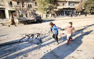 Παιδάκια επιθεωρούν τον κρατήρα που άνοιξε βόμβα της συριακής αεροπορίας σε περιοχή που ελέγχουν οι αντικαθεστωτικοί αντάρτες, στο Χαλέπι.