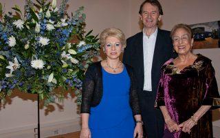Στο ανθοστόλιστο με γαλάζια και λευκά άνθη Eλληνικό Kέντρο Λονδίνου, η αναμνηστική φωτογραφία του χαρισματικού ομιλητή και φιλέλληνα Michael Wood, ιστορικού και παραγωγού ταινιών, με την ιδρύτρια της Eλληνικής Aρχαιολογικής Eπιτροπής M. Bρετανίας κ. Matti Egon και την πρόεδρο και οργανώτρια της διάλεξης Dr. Zέττα Θεοδωροπούλου.