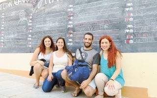 Zευγάρι επισκεπτών με την Ελενα (αριστερά) και τη Δήμητρα (δεξιά) από την ομάδα των εθελοντών, έξω από τον κινηματογράφο Θησείον και μπροστά στον μαυροπίνακα όπου πολίτες και επισκέπτες γράφουν σχόλια για την Αθήνα.