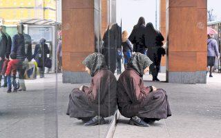 Μια γυναίκα επαίτης εκλιπαρεί για λίγα χρήματα στην είσοδο εμπορικού κέντρου στο Σεράγεβο της Βοσνίας.